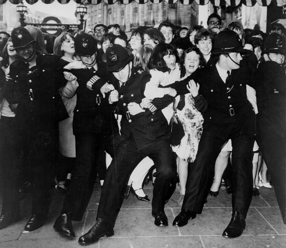 7th July 1964:  Beatles fans crowded outside the London Pavilion waiting for the band to arrive for the premiere of their first film 'A Hard Day's Night'.  (Photo by Keystone/Getty Images)