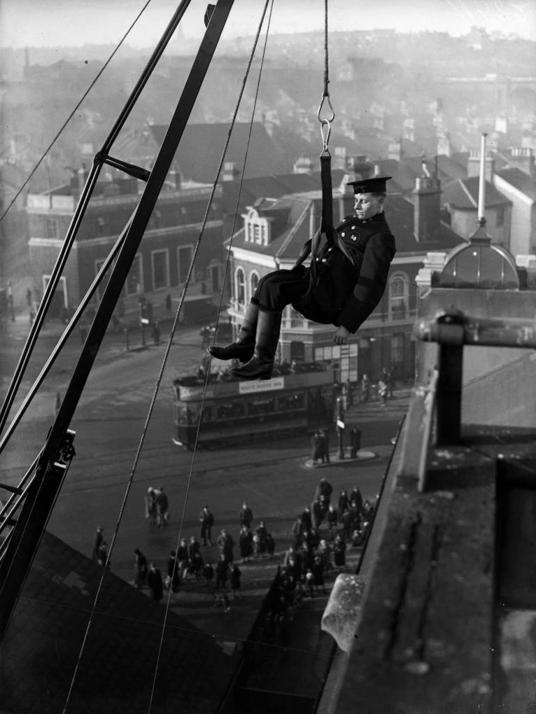 7th February 1934:  A fireman from the Brighton Fire Brigade, East Sussex, demonstrates the use of the safety belt from the top of a new 150 ft high escape.  (Photo by Reg Speller/Fox Photos/Getty Images)