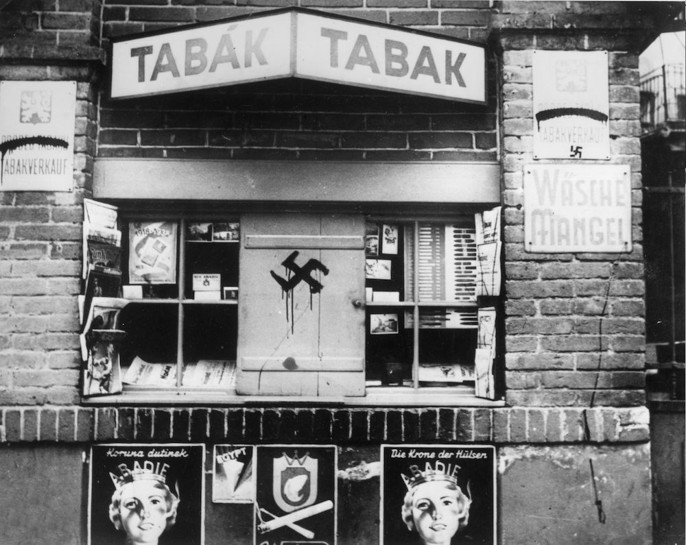 September 1938: A swastika painted onto the shutters of a 'tabak' or tobacconist in Teplitz, Sudeten Germany. This German-speaking region of Czechoslovakia was ceded to Germany in the Munich Pact of 1938, after which Czech writing was obliterated from the bilingual street signs, leaving only German text. (Photo by Keystone/Getty Images)