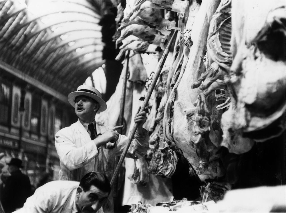 circa 1954: Carcasses hanging in a butcher's in Leadenhall Market, London. (Photo by Baron/Getty Images)