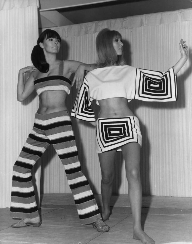 7th March 1966:  Liz Allen wearing a Lurex trouser suit and Maureen Lynne in an op-art black and white play suit  from a range of Italian knitwear fashions.  Both outfits are by Naka of Milan.  (Photo by Reg Speller/Fox Photos/Getty Images)
