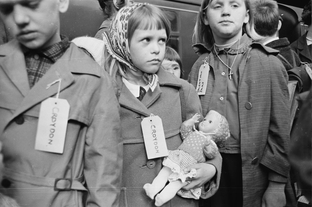 7th April 1965:  A young German girl clutches her doll for comfort. She is one of a group of German refugee children who have come to England for a holiday with an English family. She wears a label round her neck which says, 'Croydon'.  (Photo by Philip Townsend/Express/Getty Images)