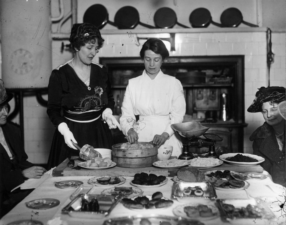 7th February 1918:  Mrs Weighall and her cook demonstrating how using potatoes and rice can save flour.  (Photo by Topical Press Agency/Getty Images)