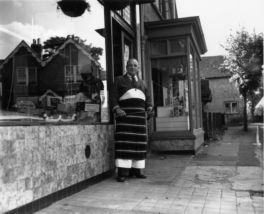 19th August 1953: A village butcher stands outside his shop in Shere, Surrey. Reflected in his shop window are typical Surrey houses. (Photo by T. Marshall/Topical Press Agency/Getty Images)
