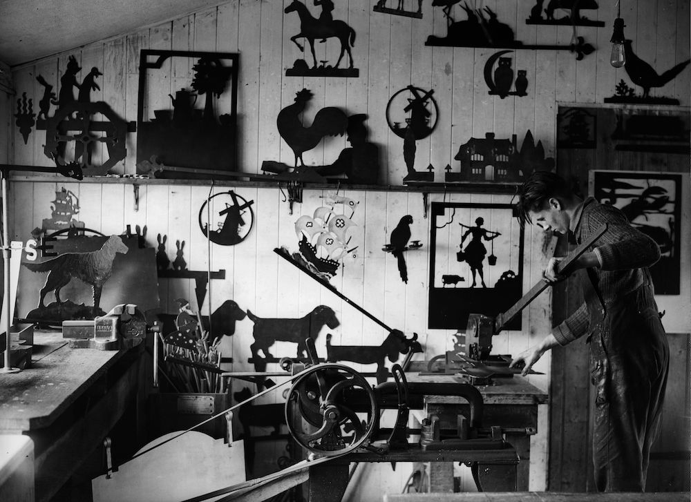 7th January 1932:  Captain G C Clark, whose favourite artistic medium is sheet metal creates one of his two-dimensional sculptures in his already crowded workshop.  (Photo by Fox Photos/Getty Images)