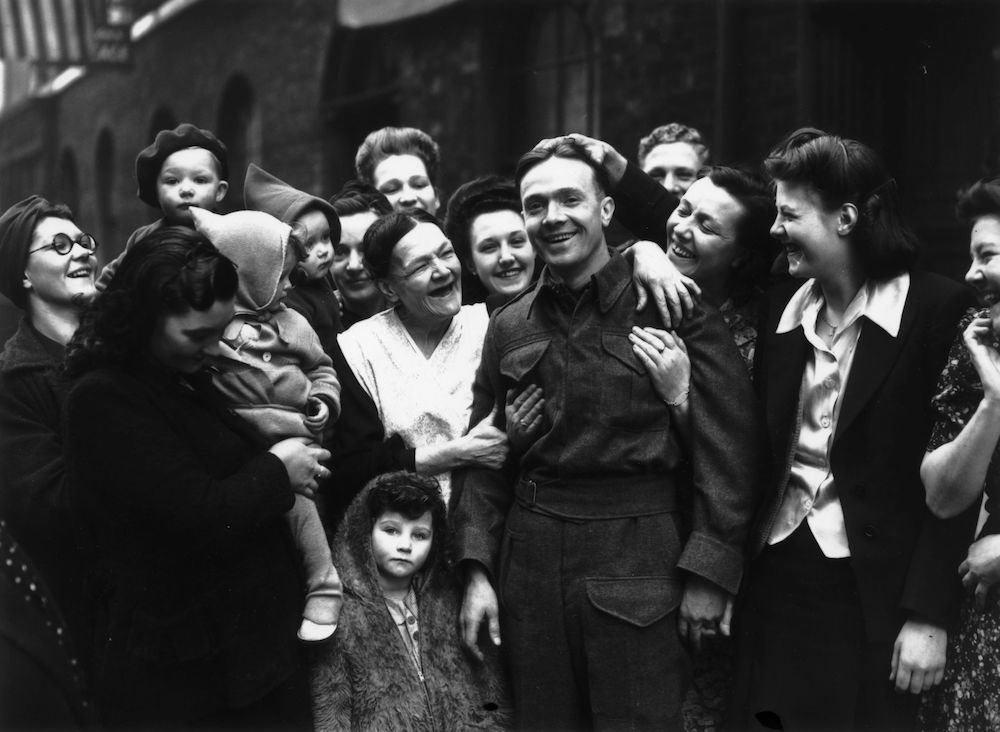 7th February 1945:  Private Fred Poulten arrives home in Clerkenwell to a hero's welcome by his mother and friends. He has been repatriated after being taken prisoner at Dunkirk during World War II.  (Photo by Reg Speller/Fox Photos/Getty Images)