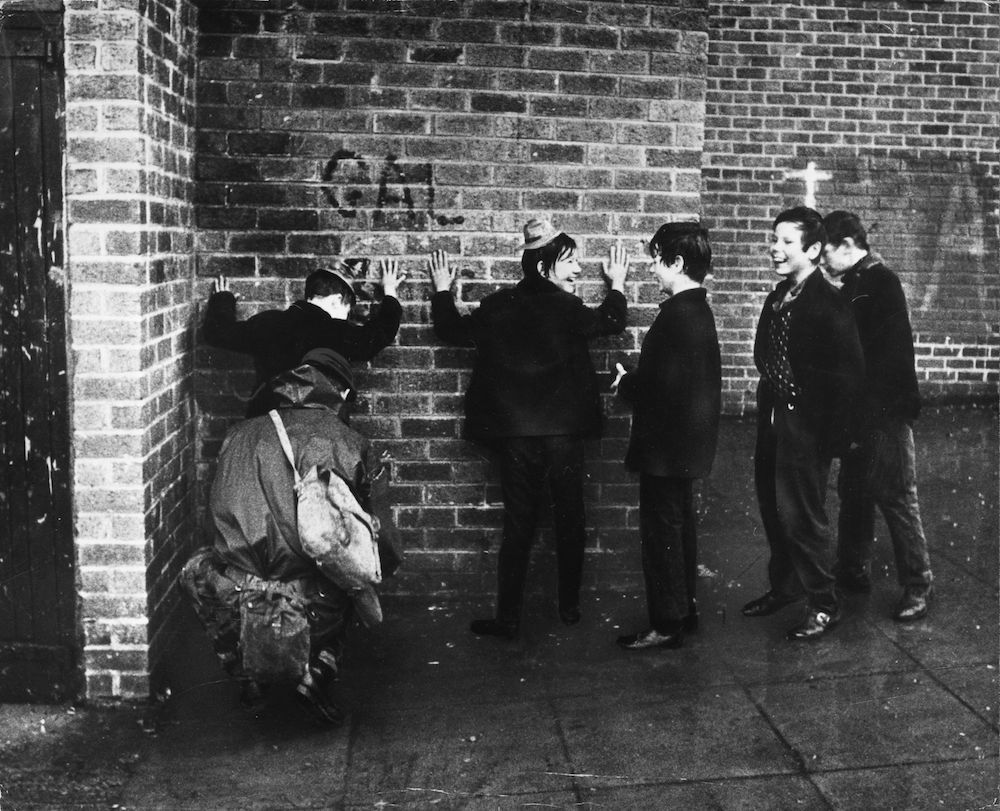 7th December 1971:  Schoolboys giggling while a soldier searches them in a street in the Ardoyne area of Belfast.  (Photo by Keystone/Getty Images)