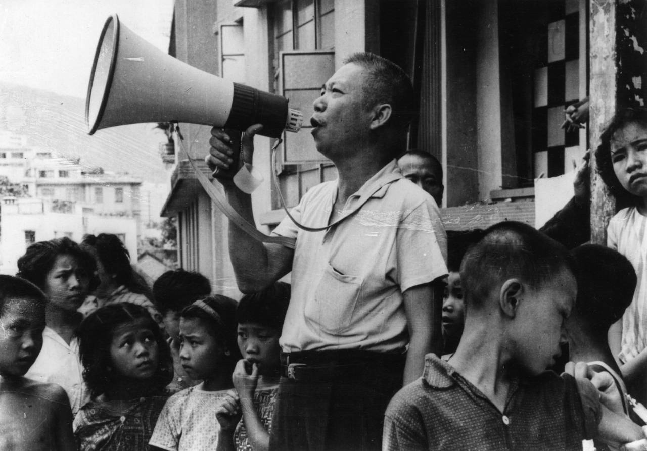 7th August 1963:  A man using a loudhailer to call people to inoculation centres in Hong Kong, following an outbreak of Cholera. 16 people have so far been diagnosed as having the disease, and those who have had contact with the illness have been placed in isolation camps.  (Photo by Keystone/Getty Images)