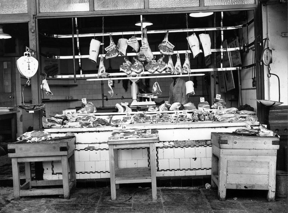 7th August 1954: Meat hanging in a butcher's shop in Smithfield market, London is clearly labelled with price and country of origin. (Photo by Monty Fresco Jnr/Topical Press Agency/Getty Images)