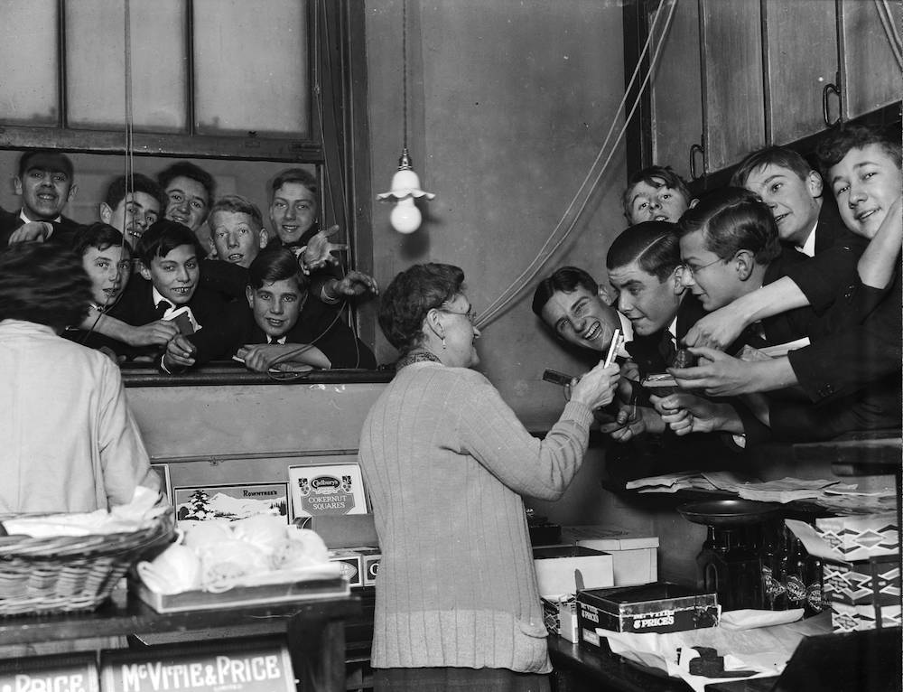 December 1928: Mrs Rouse serves pupils in the tuckshop at Westminster School, London. (Photo by Fox Photos/Getty Images)
