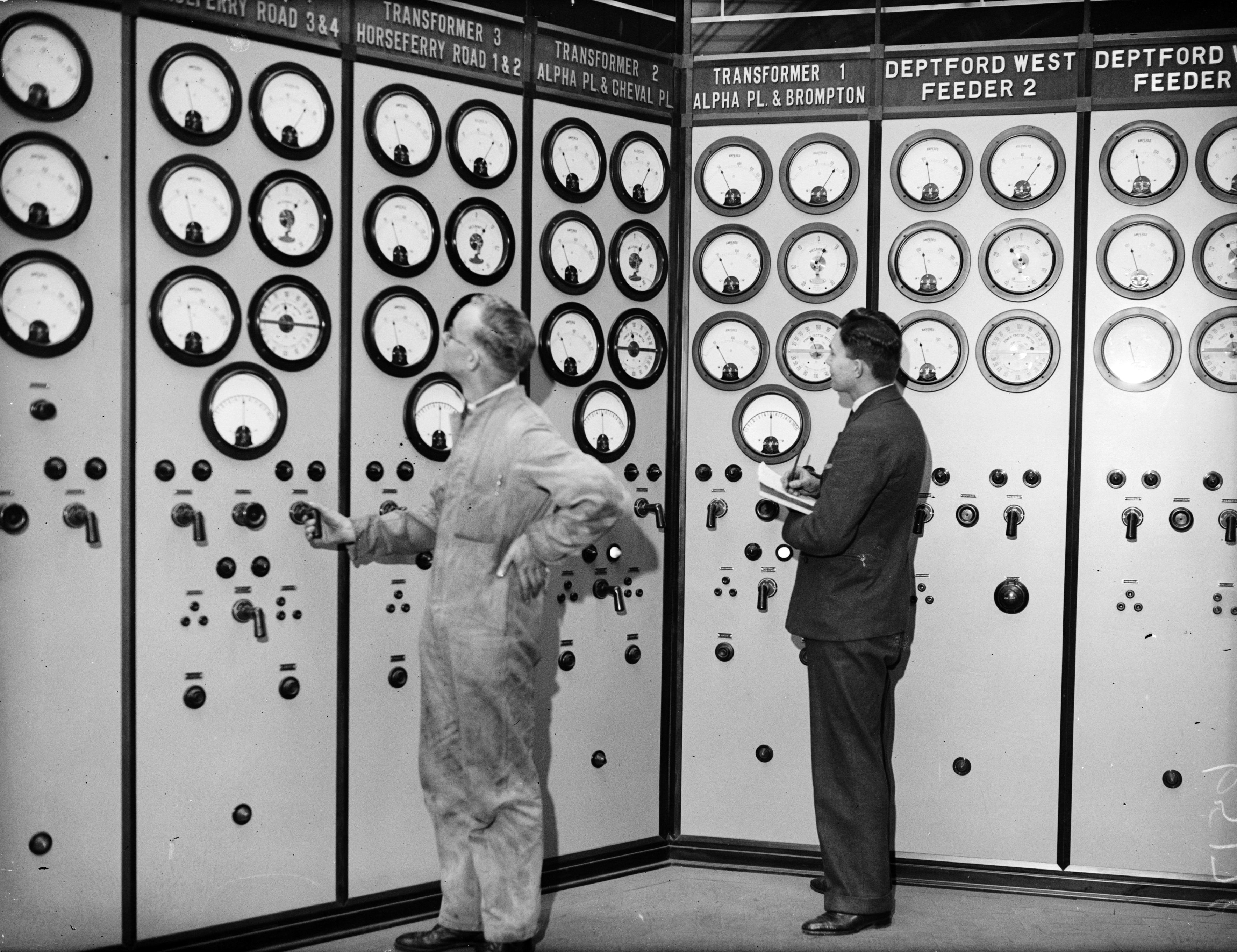 10th December 1932: Technicians consult a wall of dials for readings from the transformers and feeders at the Battersea Power Station, London. (Photo by Fox Photos/Getty Images)