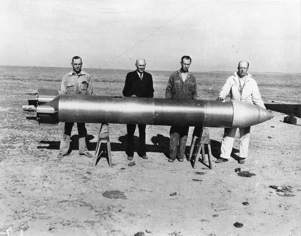 7th November 1936:  Rocket pioneer Dr Robert Hutchings Goddard (1882 - 1945), second from left, and his four stage rocket.  (Photo by Hulton Archive/Getty Images)