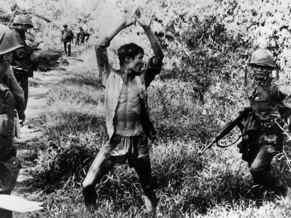7th November 1967:  A Viet Cong suspect holds his hands up after a Vietnamese Ranger from the 21st Vietnam Infantry Division routed him from his hiding place.  (Photo by Keystone/Getty Images)