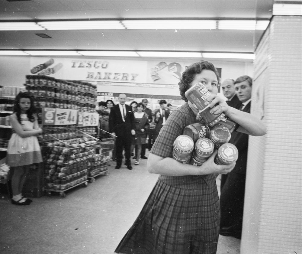 10th August 1966: Mrs Buzidragis, winner of a US supermarket sweep contest attempts to repeat her prize-winning feat in a London Tesco. She makes her way to the checkout counter with her arms full of Maxwell House coffee jars. (Photo by Terry Fincher/Express/Getty Images)
