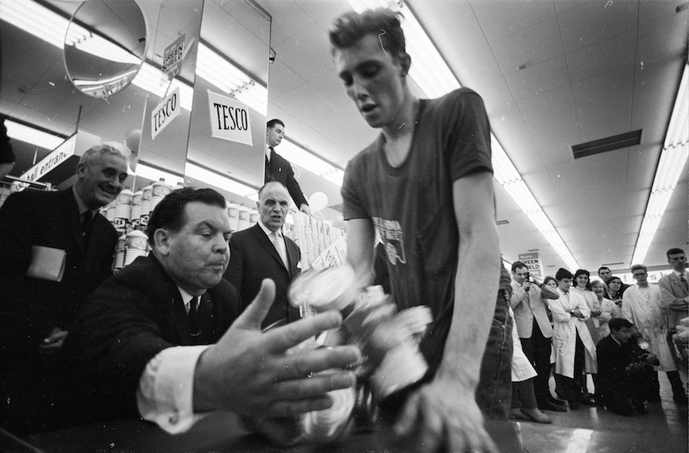 10th August 1966: Joe Buzidragis, whose parents won a US supermarket sweep contest helps them repeat their prize-winning feat in a London Tesco. (Photo by Terry Fincher/Express/Getty Images)
