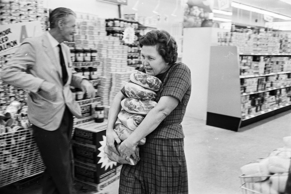 10th August 1966: Mrs Buzidragis, winner of a US supermarket sweep contest attempts to repeat her prize-winning feat in a London Tesco. (Photo by Terry Fincher/Express/Getty Images)