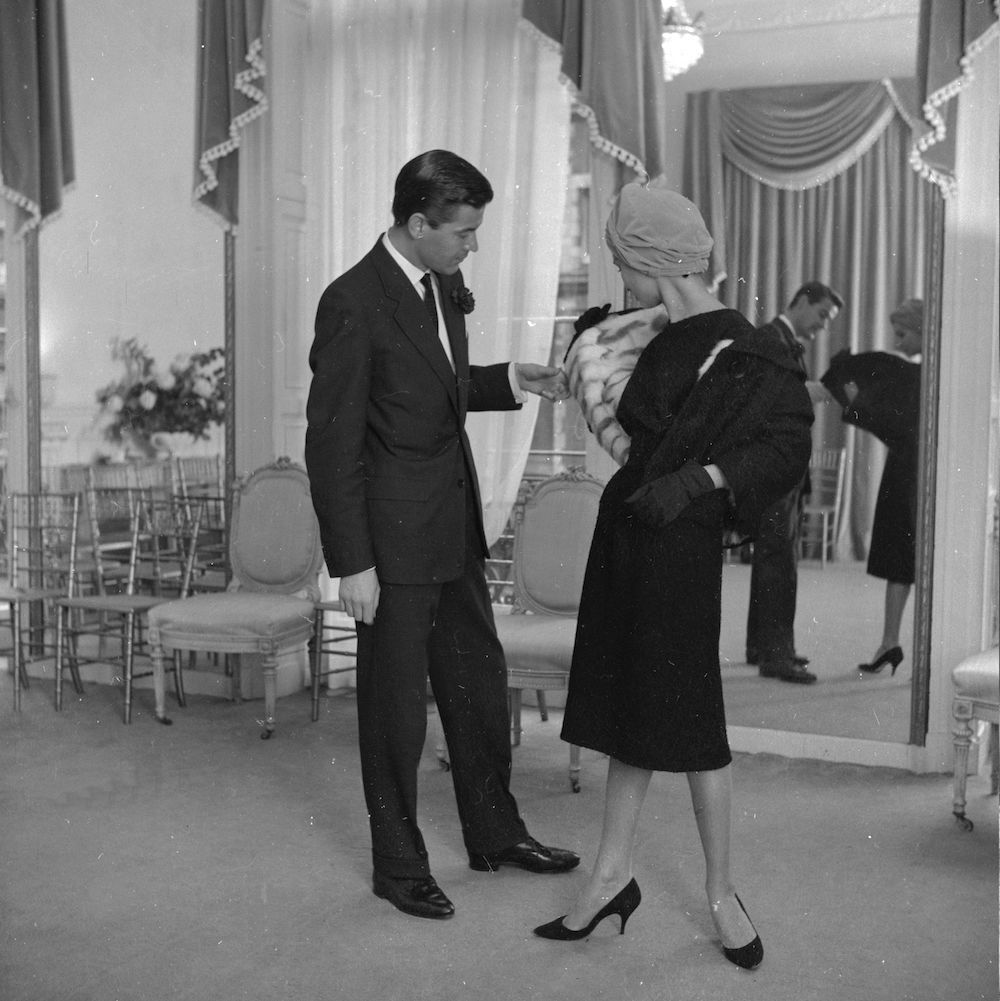 1958: Anglo-Indian fashion model Liat Sands models in the Mayfair salon of top couturier Ronald Paterson. Her boyfriend Ken Swift admires the squirrel fur lining of her dress and jacket. (Photo by Rosemary Matthews/BIPs/Getty Images)