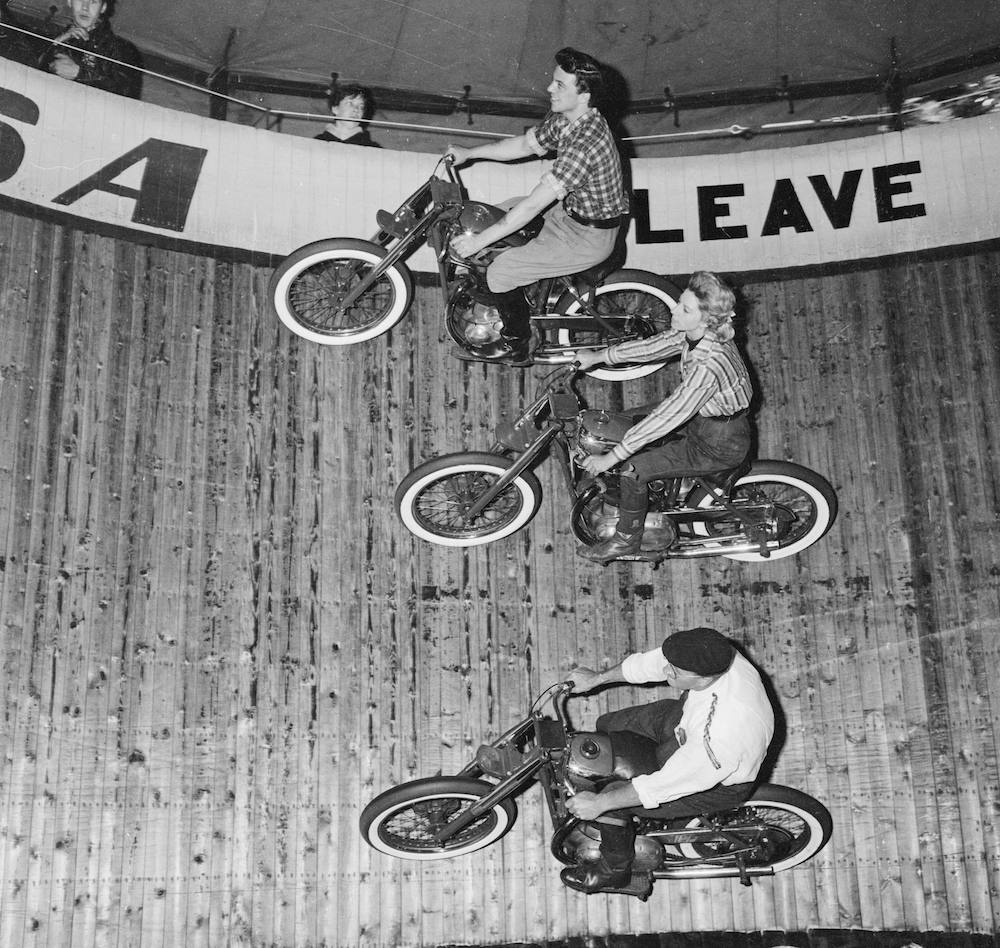 24th June 1963:  Cindy Willis, a Wall of Death rider at Canvey Island, flanked by two other riders.  (Photo by C. Leech/Express/Getty Images)