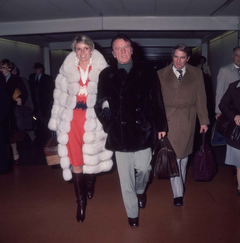 1977: Actor Richard Burton (1925 - 1984) and his wife Susan Hunt at Heathrow airport. (Photo by Fox Photos/Getty Images)