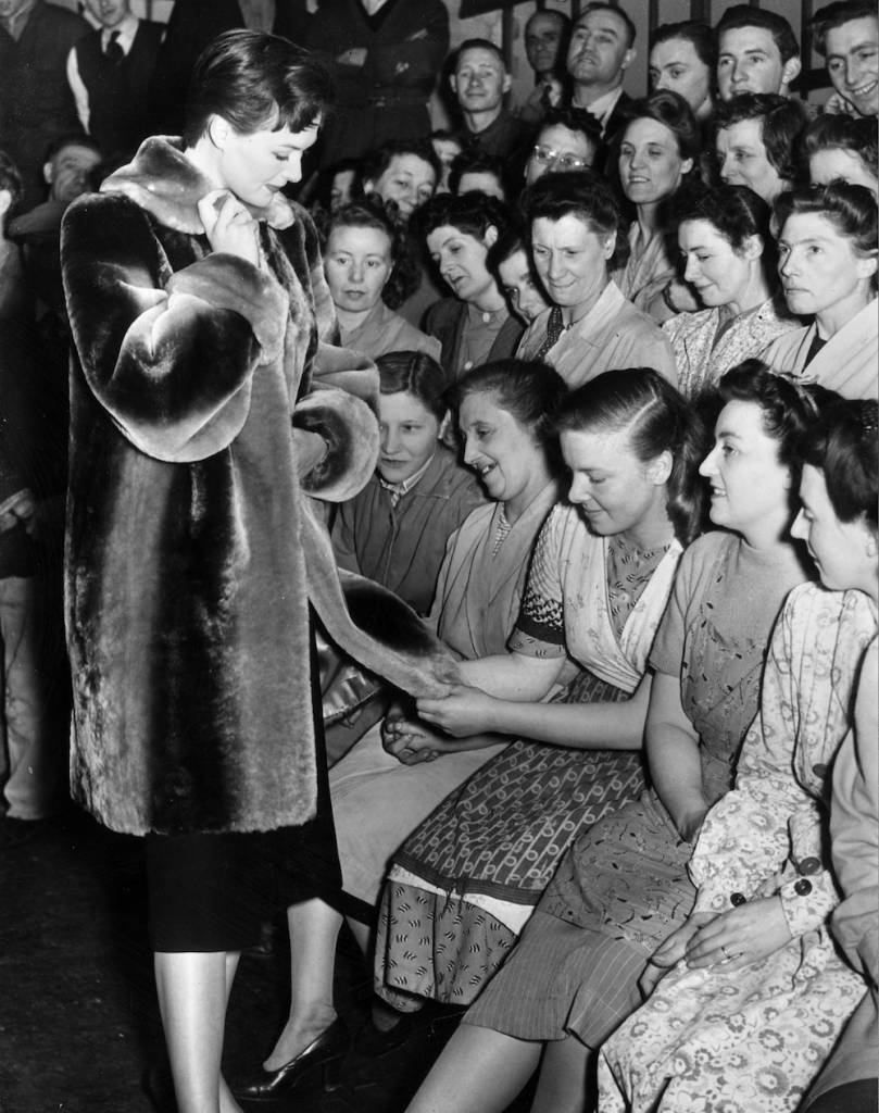26th April 1950: A woman worker at the Alaska Fur works in Bermondsey, London, where skins are prepared, feels the texture of a 'phantom' beaver fur coat worn by a mannequin during a lunch time fashion parade. The coat costs about ?32. (Photo by Fred Morley/Fox Photos/Getty Images)