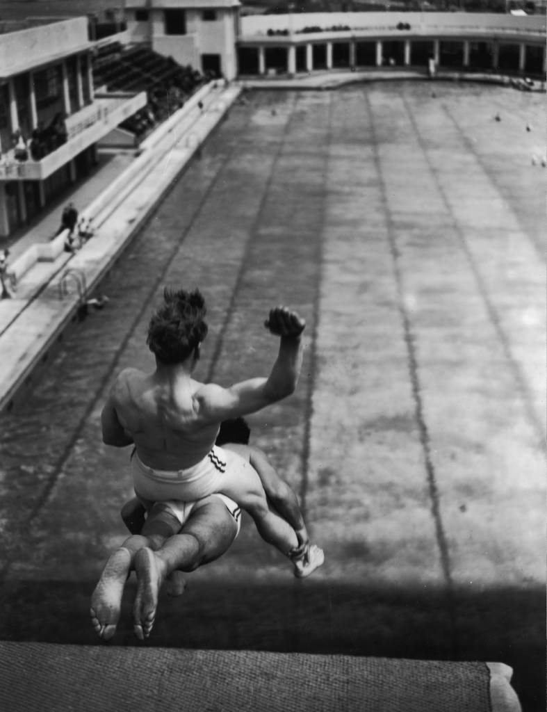 7th July 1939:  Schmidt and Marco, stunt divers at Morecambe, Lancashire. One dives into a swimming pool with the other astride his hips.  (Photo by Fox Photos/Getty Images)
