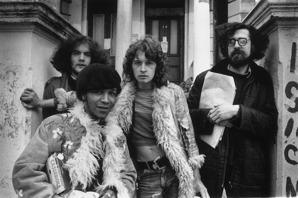 15th October 1974: Three squatters (Ger Ryan, Alex Innis and Chris Sparrow) outside their house at 19 Elgin Avenue, central London. Note the fashionable Afghan coats worn by two of the young hippies. (Photo by Evening Standard/Getty Images)