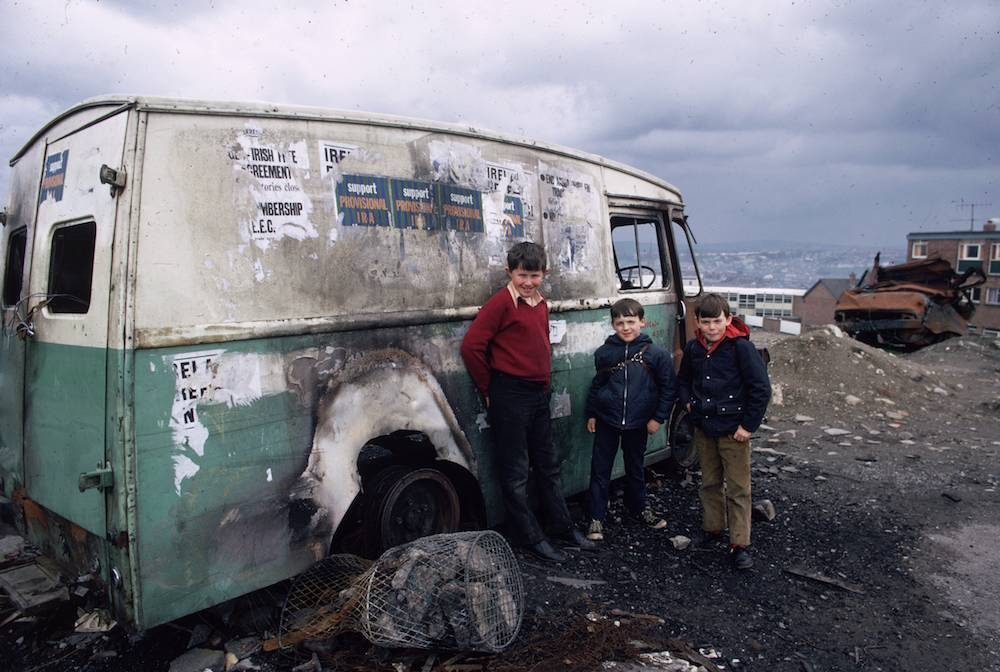 circa 1975: Three children gather by a burnt out van plastered with IRA posters, in the predominantly Catholic Bogside area of Londonderry. (Photo by Keystone/Getty Images)