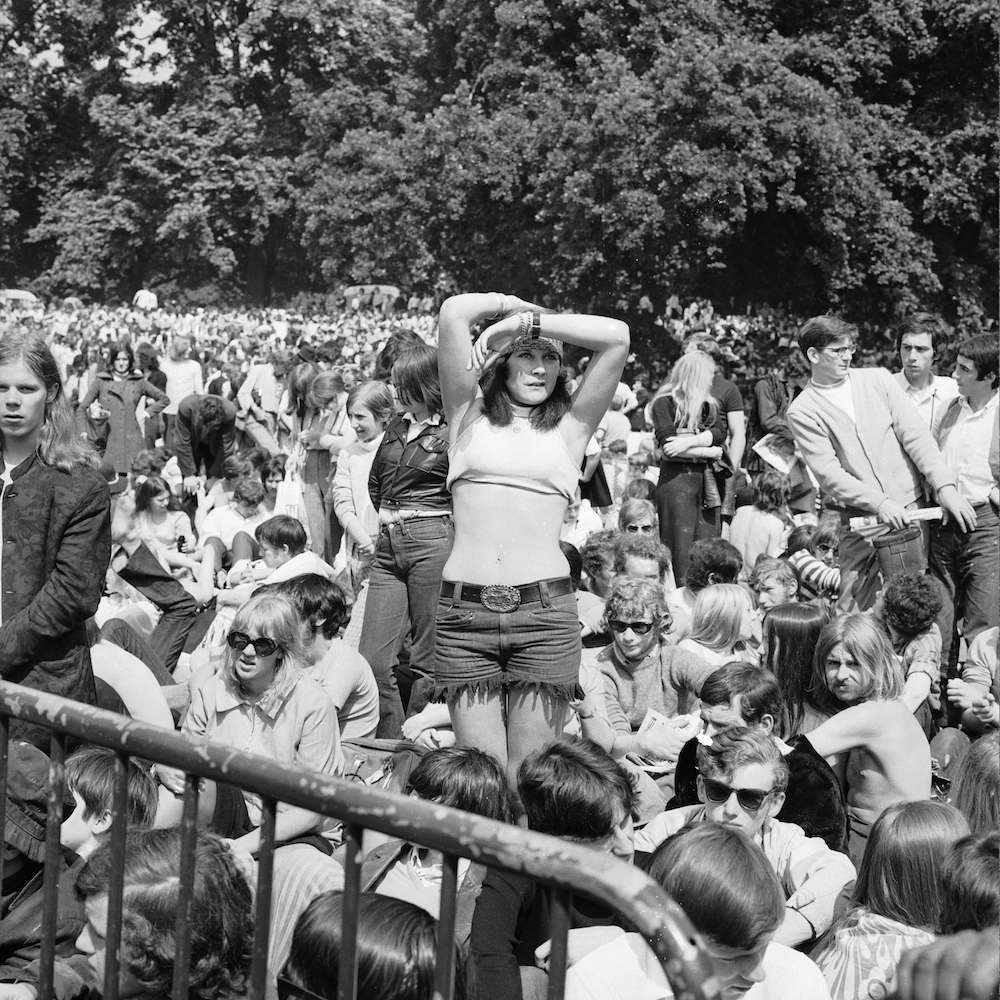 5th July 1969: A woman in a cropped top and cut-off shorts standing among people gathered in Hyde Park to see the Rolling Stones in concert. (Photo by Reg Burkett/Express/Getty Images)