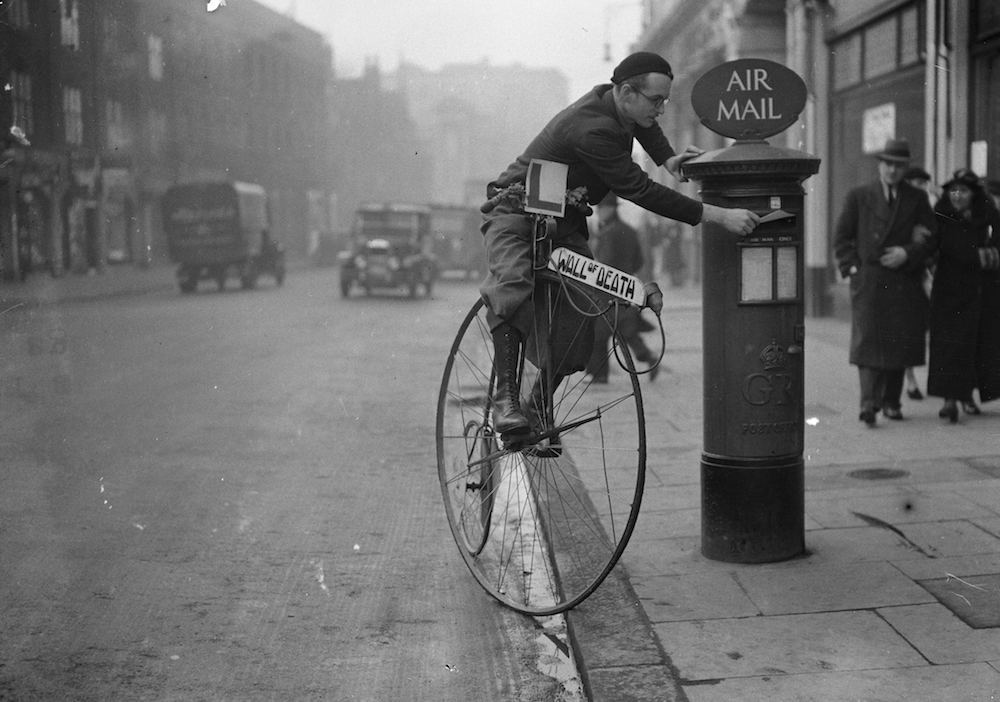 23rd December 1936: Mr Tornado Smith posts a letter while riding penny farthing bicycle. He is wearing a learner plate and his bike is advertising his Wall of Death act. (Photo by Derek Berwin/Fox Photos/Getty Images)