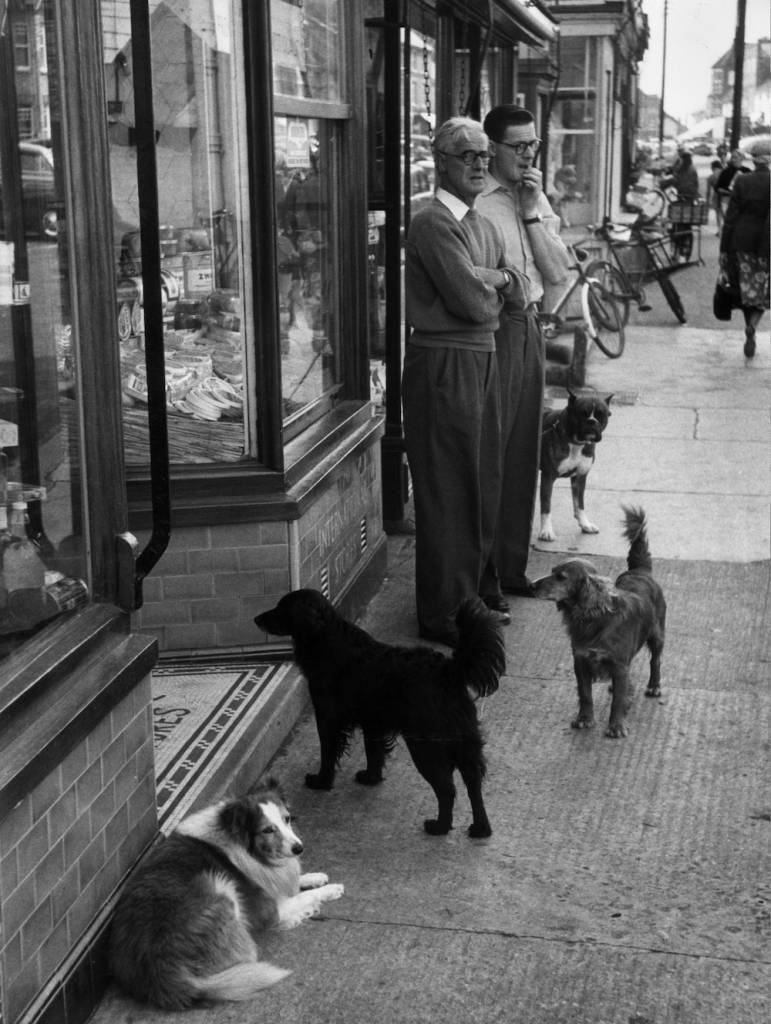 1949: A group of dogs and two hungry looking men loitering outside a butcher's shop in Aldeburgh. (Photo by Kurt Hutton/Hulton Archive/Getty Images)