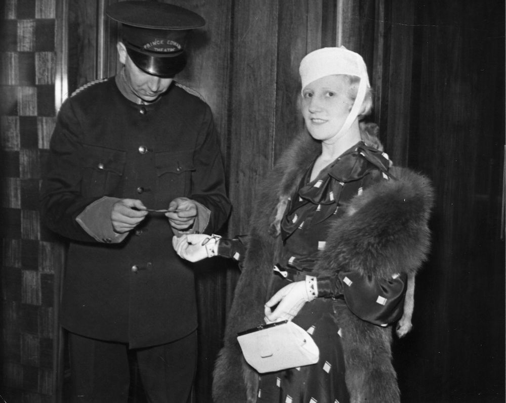 1st July 1932: A woman shows her ticket to a doorman for the first night of the play 'Fanfare' at the Prince Edward Theatre in London. (Photo by Sasha/Getty Images)