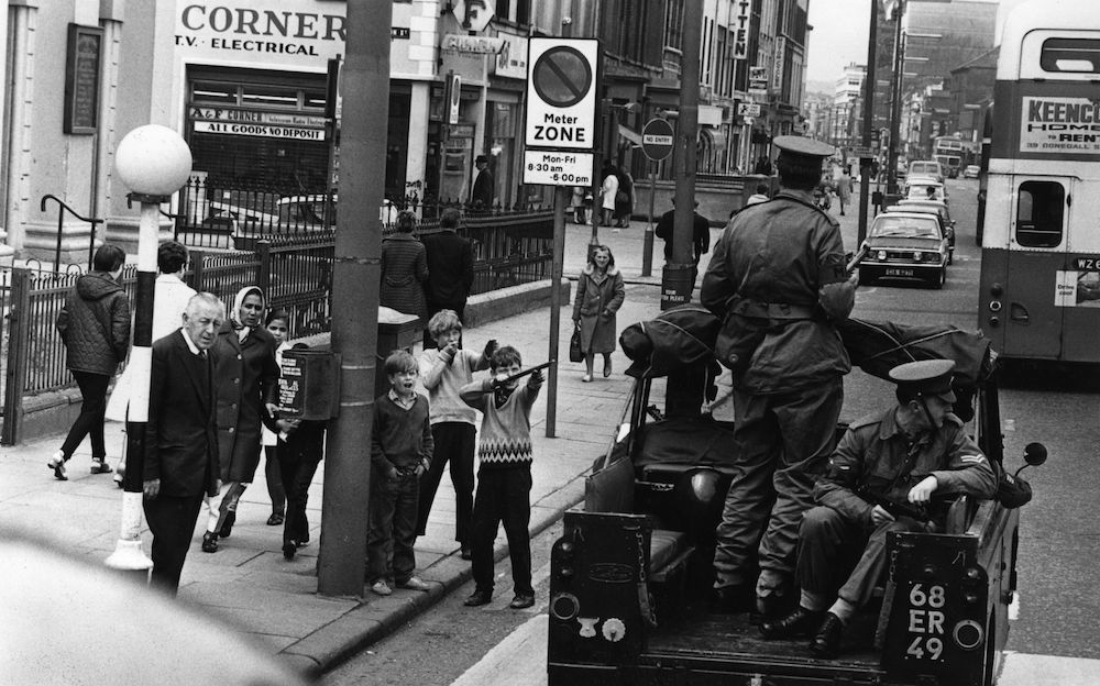 July 1970: Children mocking an Army patrol in Belfast. (Photo by Malcolm Stroud/Express/Getty Images)