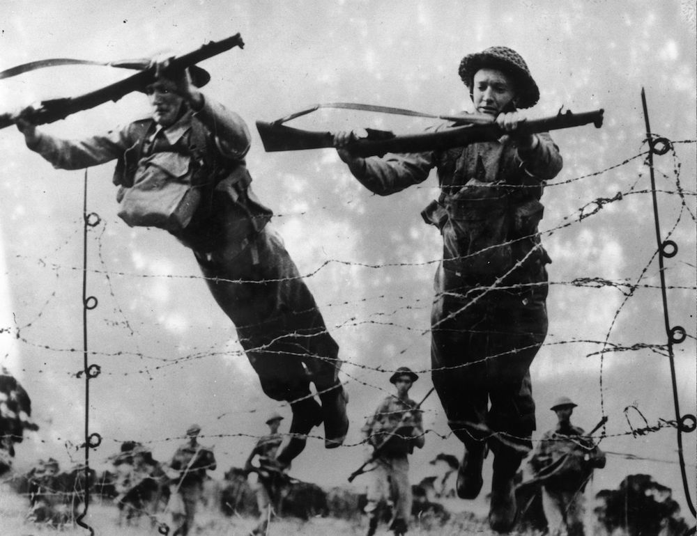 7th July 1942:  Australian soldiers throw themselves onto barbed wire during training to let other troops pass over more comfortably.  (Photo by Keystone/Getty Images)