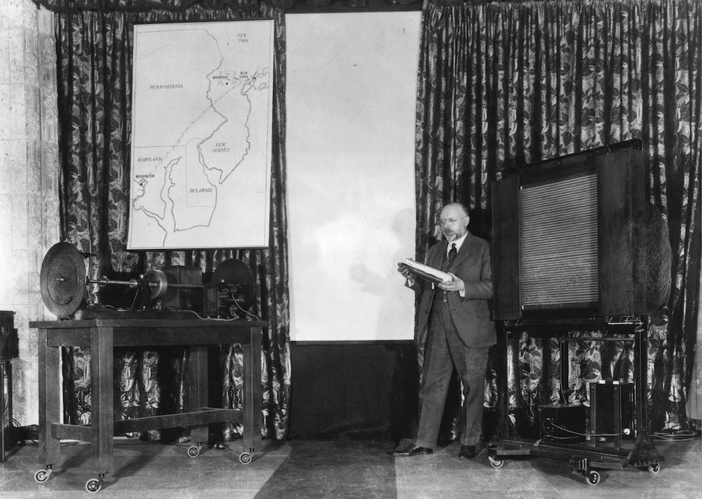 7th April 1927:  The director of electro-optical research at Bell Telephone Laboratories, Doctor Herbert Ives,  beside a television receiving the first inter-city broadcast.  (Photo by Hulton Archive/Getty Images)