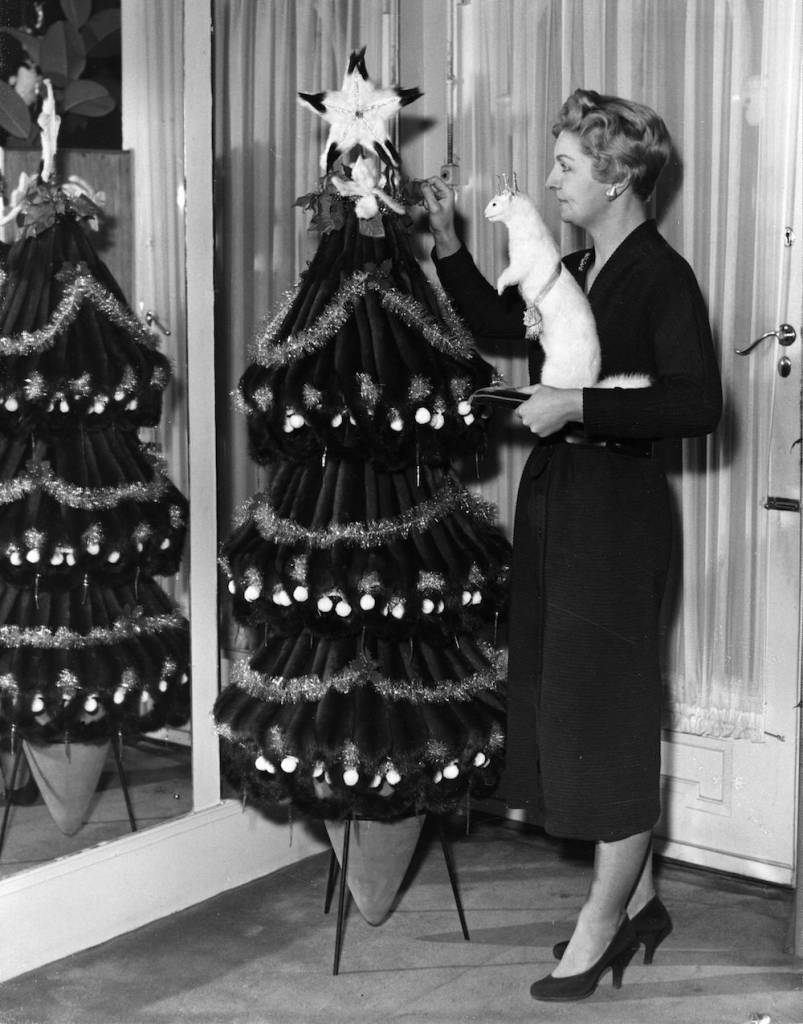 22nd November 1956: On display in a Mayfair, South Moulton Street fur showroom, Eileen O'Mara, is holding a stuffed white mink worth ?75 and is fixing the trimmings on the tree, valued at ?4,200. It is made entirely of 100 Canadian wild mink skins. (Photo by Fox Photos/Getty Images)