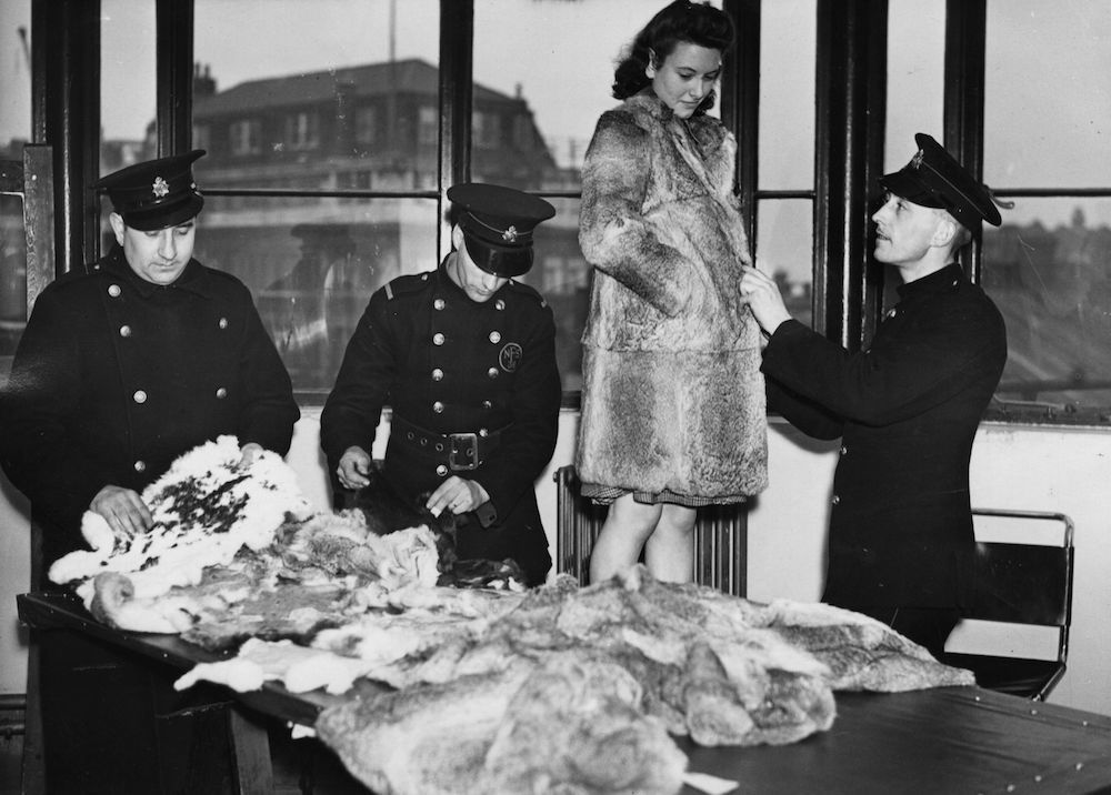 30th November 1943: East London firemen sorting skins while a woman tries on a fur coat made of rabbit skins to be displayed at the London Fire Forces 'Off the Ration' Exhibition, in aid of children in Russia. (Photo by Harry Todd/Fox Photos/Getty Images)