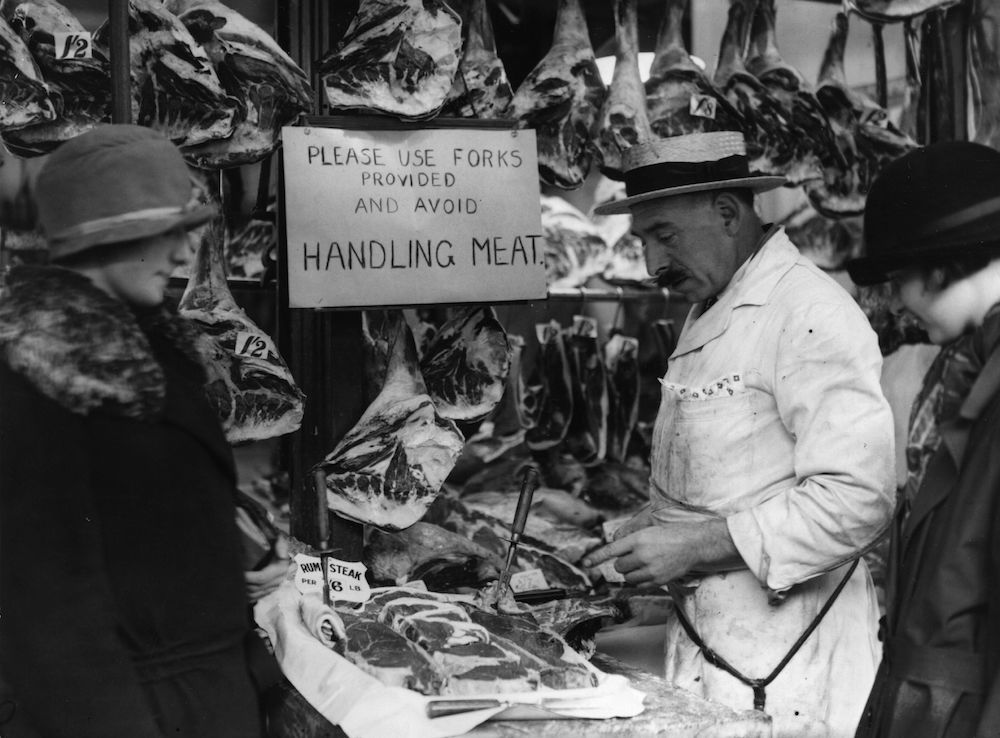 30th December 1924: A Smithfield butcher at work with many carcasses and joints hung up around him. (Photo by MacGregor/Topical Press Agency/Getty Images)