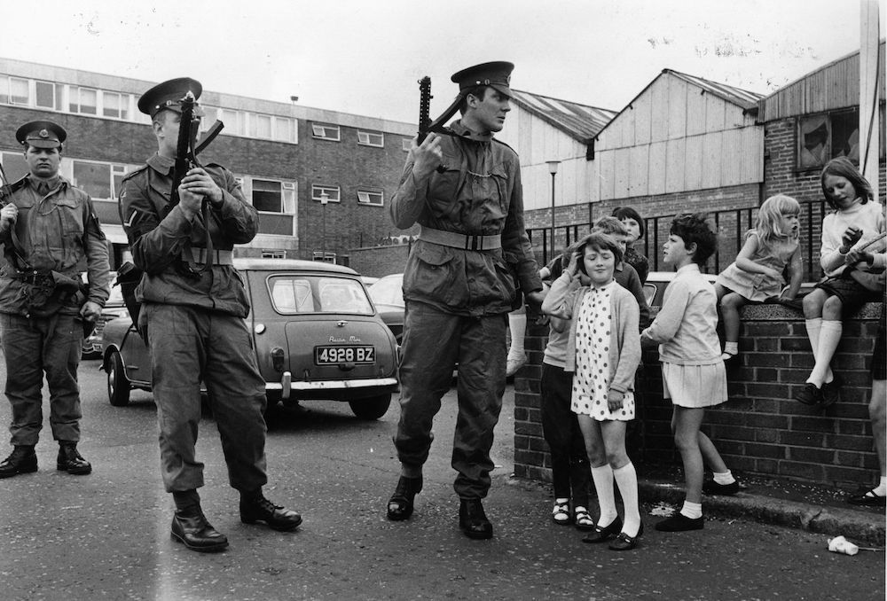 July 1970: Armed British soldiers impose a curfew on the Falls Road in Belfast. (Photo by Malcolm Stroud/Express/Getty Images)