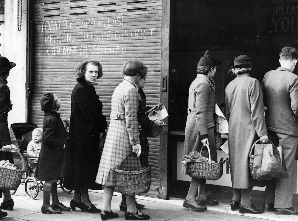 7th April 1943:  Shoppers queue for their fish in Eltham.  This particular shopkeeper has posted a notice that only local people will be served and identity cards inspected before the purchase can be made.  (Photo by Fox Photos/Getty Images)