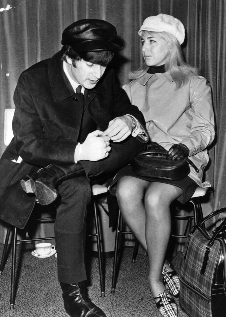 7th February 1964:  Singer and songwriter John Lennon (1940 - 1980), of British pop group The Beatles, and his wife Cynthia wait for a flight to New York at London Airport. John is wearing the 15 guinea Mary Quant hat that sparked a recent trend.  (Photo by Evening Standard/Getty Images)