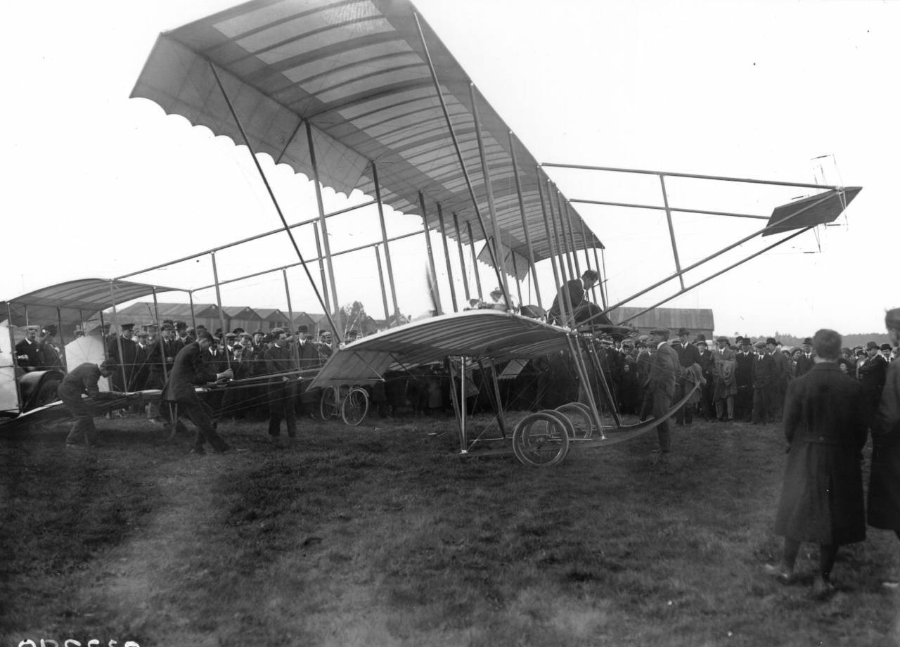 24th April 1911: A crowd at Brooklands gathers to watch a Bristol Box Kite bi-plane take off, with pilot Gilmour perched precariously above the wheels.