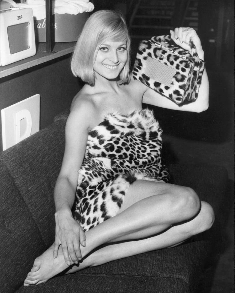 circa 1964: Louise Cigarini wearing a leopardskin outfit holds up the new leopardskin Roberts Radio 500 at the press preview of the 1964 TV and Radio Show at Earls Court. (Photo by Keystone/Getty Images)