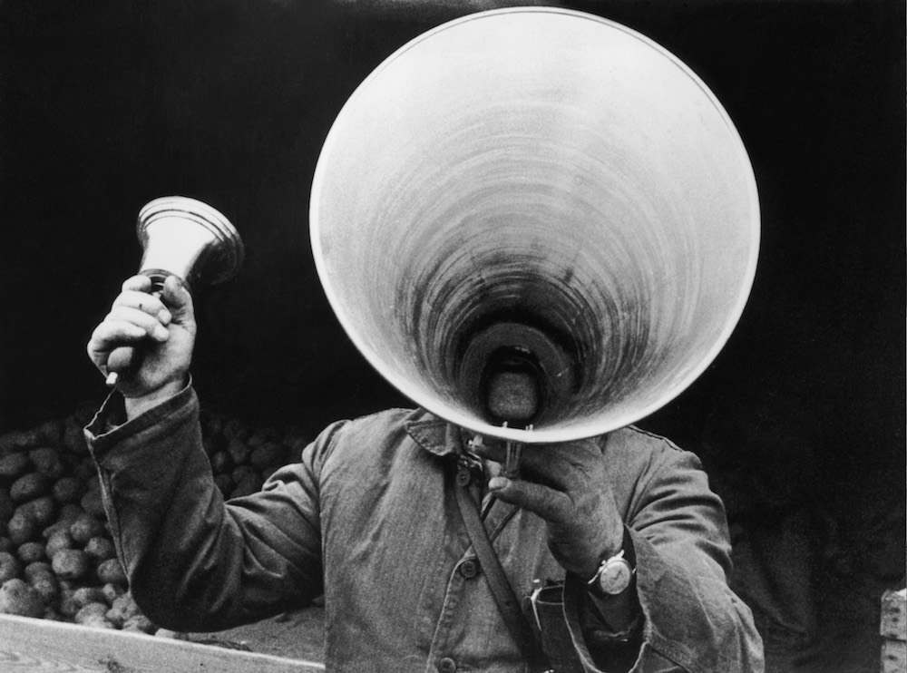7th April 1963:  A potato vendor in Berlin uses a bell and a megaphone to attract customers.  (Photo by Keystone/Getty Images)