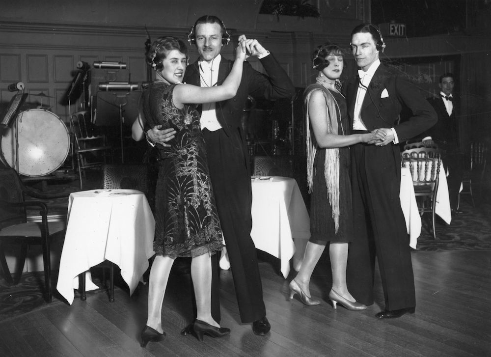 1st March 1928:  Couples dancing with wireless earphones.  (Photo by Fox Photos/Getty Images)