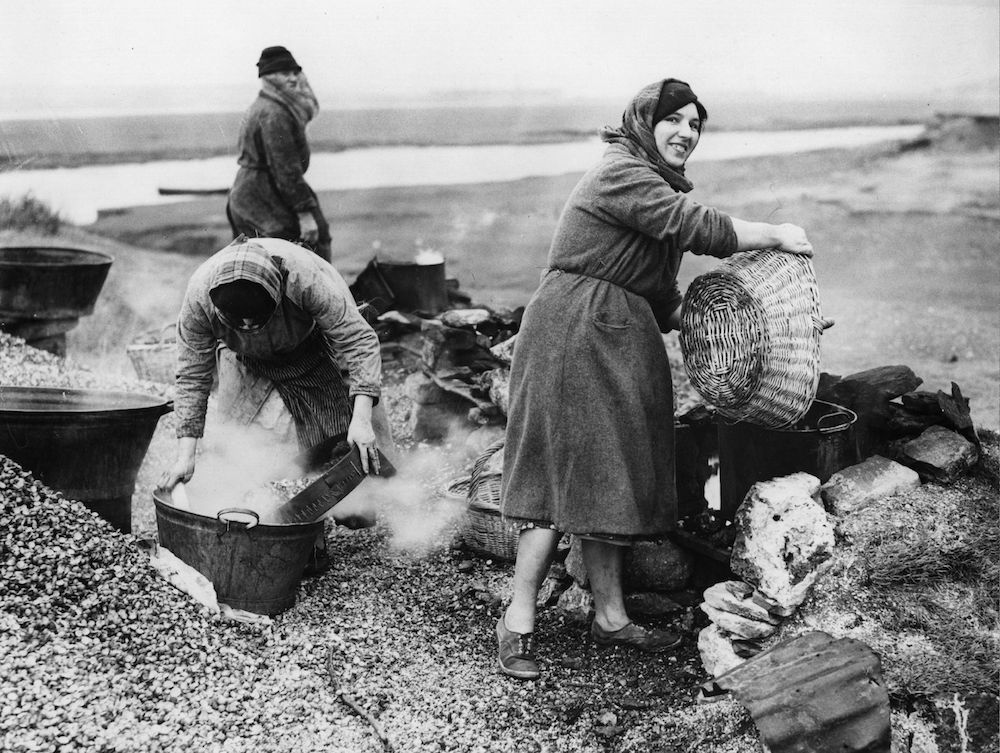 7th December 1938:  The cocklewomen of Penclawdd in South Wales at work boiling and cleaning their catch. They are endeavouring to form themselves into a company now that a number of the old style fish bars have closed, thus threatening their trade. This would enable them to open a modern cleaning plant in the village.  (Photo by Fox Photos/Getty Images)
