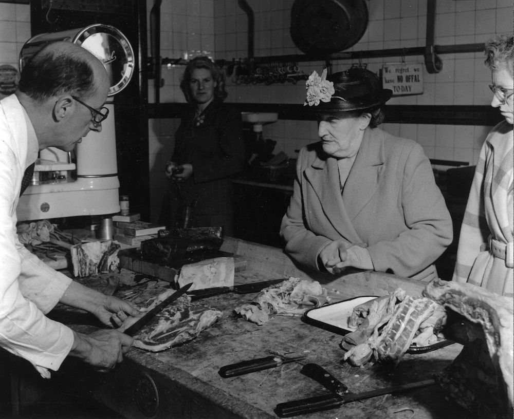 circa 1954: A woman customer watches the butcher slice-up a joint of meat. (Photo by Hulton Archive/Getty Images)