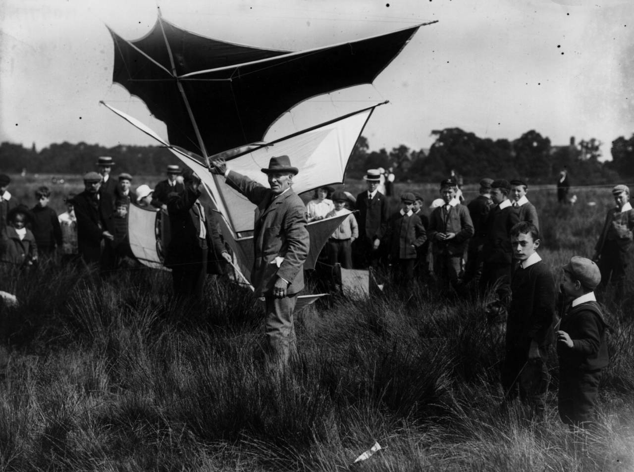 1908: A Brogdani dihedral kite being held ready for launch while a group of youths look on.