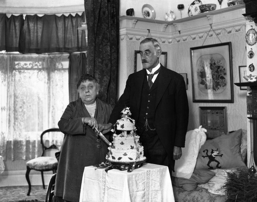 7th September 1931:  Mr W Knightsmith, a London toastmaster celebrating his golden wedding, cuts a cake with his wife.  (Photo by A. Hudson/Topical Press Agency/Getty Images)