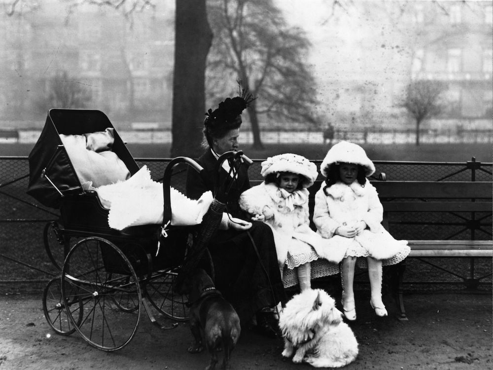 1911: A nursemaid sits with her two young charges, who are dressed in pale fur-trimmed coats, hats and gloves, next to a pram and two dogs in Hyde Park, London. (Photo by Topical Press Agency/Getty Images)