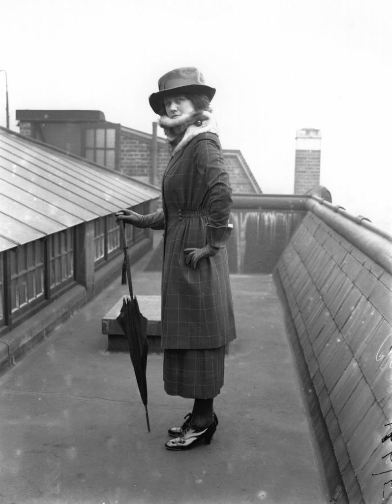 1921: A model posing on a roof-top and wearing a ruched-waist suit from Burberry's, London, with fur collar and gauntlet gloves. (Photo by Central Press/Getty Images)